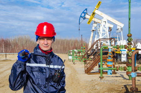 pump jack: Portrait of man engineer in the oil field wearing red helmet and work clothes holding wrenches in his hand and radio in jacket pocket. Blurry pump jack and wellhead background. Oil and gas concept. Stock Photo