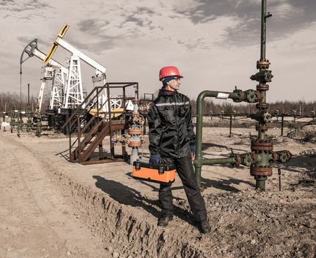 wellhead: Man engineer in the oil field wearing red helmet and work clothes holding toolbox and wrenches in his hand and radio in jacket pocket. Pump jack and wellhead background. Oil and gas concept. Toned. Stock Photo
