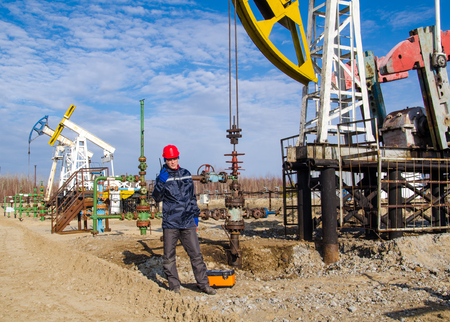 pump jack: Man engineer in the oil field wearing red helmet and work clothes talking on the radio. Pump jack and wellhead background. Oil and gas concept. Stock Photo