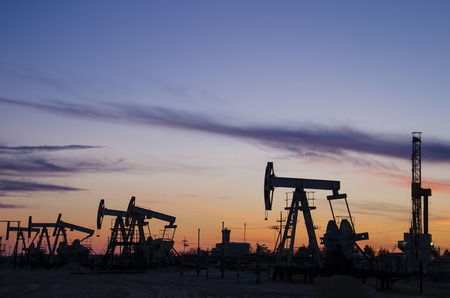 jacks: Pump jacks and derrick silhouette during sunset on the oilfield. Oil and gas concept. Stock Photo