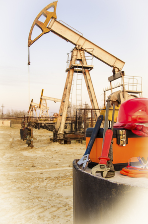 bussines people: Tool box, helmet and wrenches on the background of blurry pump jack. Oil and gas concept. Toned.