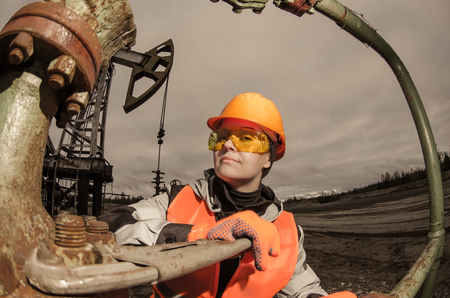 wellhead: Woman engineer in the oil field repairing wellhead with the wrench wearing orange helmet and work clothes. Oil and gas concept. Fish eye shot. Toned.