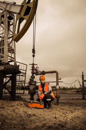 pump jack: Woman engineer in the oil field repairing wellhead with the wrench wearing orange helmet and work clothes. Pump jack and wellhead background. Oil and gas concept. Stock Photo