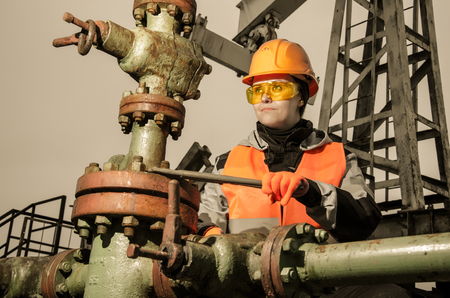 wellhead: Woman engineer in the oil field repairing wellhead with the wrench wearing orange helmet and work clothes. Oil and gas concept. Toned.