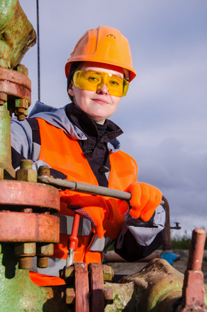Woman engineer in the oil field repairing wellhead with the wrench wearing orange helmet and work clothes. Oil and gas concept. Stock Photo