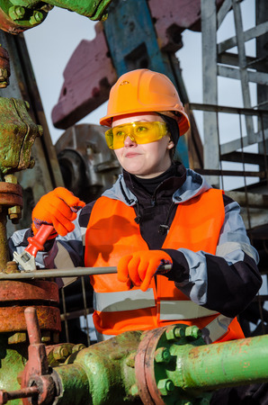 wellhead: Woman engineer in the oil field repairing wellhead with the wrench wearing orange helmet and work clothes. Oil and gas concept. Stock Photo
