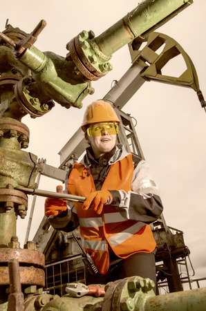 Woman engineer in the oil field repairing wellhead with the wrench wearing orange helmet and work clothes. Pump jack background. Oil and gas concept. Toned.