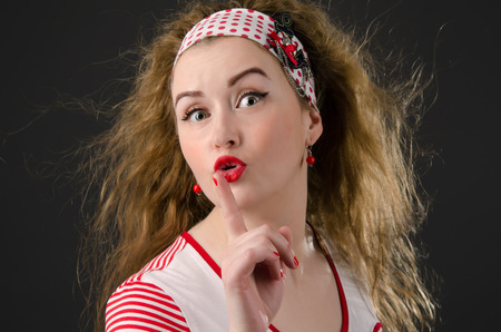 Beautiful young pin-up woman asking for silence. Girl wearing red cloths with radiant red lipstick. Dark background.