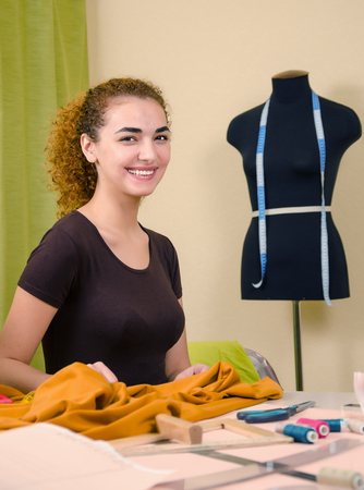 tailor shop: Young beautiful female tailor working in the tailor shop. Dummy, textile and sewing accessories background. Stock Photo