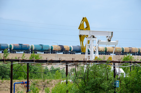 well head: Pump jack, well head and pipeline on the background of moving tank train. Oil and gas concept.