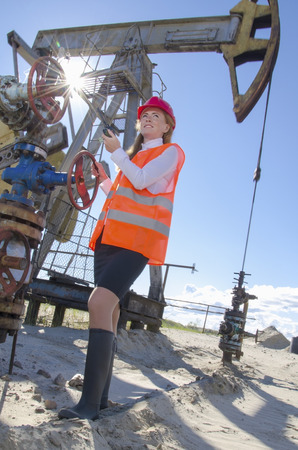 wellhead: Woman engineer in the oil field talking on the radio wearing red helmet and work clothes. Pump jack and wellhead background. Oil and gas concept.