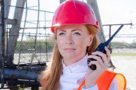 pump jack: Beautiful woman engineer in the oil field talking on the radio wearing red helmet and work clothes. Pump jack background. Oil and gas concept. Stock Photo