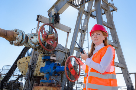 well head: Beautiful woman engineer near well head valve in the oil field talking on the radio wearing red helmet and work clothes. Pump jack background. Oil and gas concept.