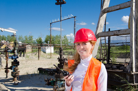 well head: Beautiful woman engineer near well head in the oil field talking on the radio wearing red helmet and work clothes. Pump jack and pipeline background. Oil and gas concept. Stock Photo