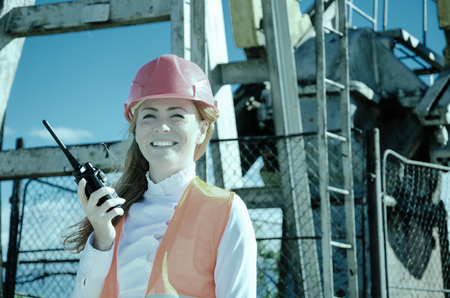 pump jack: Beautiful woman engineer in the oil field talking on the radio wearing red helmet and work clothes. Pump jack background. Oil and gas concept. Toned.