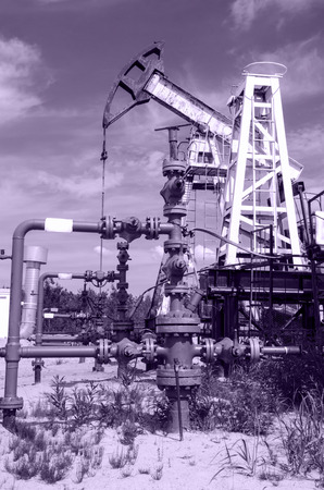 wellhead: Pump jack and wellhead in the oilfield. Oil and gas concept. Toned.