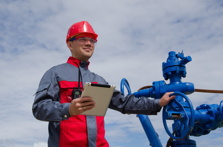 Worker near well head valve holding tablet computer and wearing red helmet in the oilfield. Oil and gas concept.