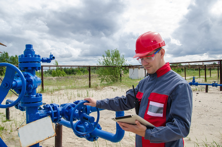 well head: Worker near well head valve holding tablet computer and wearing red helmet in the oilfield. Oil and gas concept.
