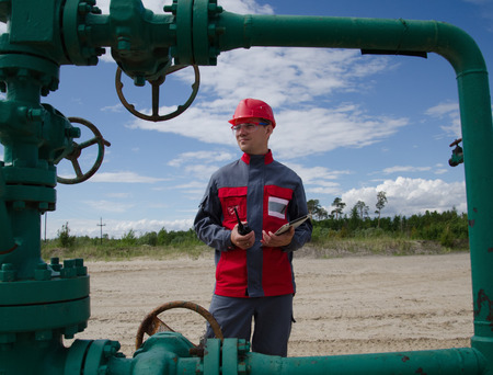 well head: Worker near well head valve holding tablet computer and radio and wearing red helmet in the oilfield. Oil and gas concept. Stock Photo