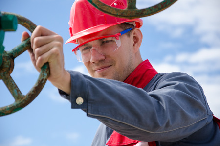 Oilfield worker near well head valve wearing red helmet. Oil and gas concept.