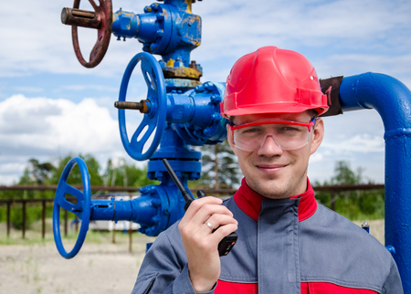 well head: Worker near well head valve holding radio and wearing red helmet in the oilfield. Oil and gas concept.
