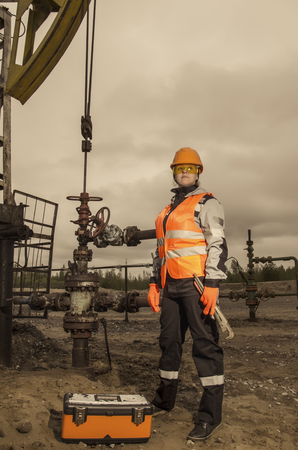 pump jack: Woman engineer in the oil field with the wrench and toolbox wearing orange helmet and work clothes. Pump jack background. Oil and gas concept. Toned.