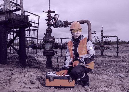wellhead: Woman engineer in the oil field with the wrench and toolbox wearing orange helmet and work clothes. Pump jack and wellhead background. Oil and gas concept. Toned. Stock Photo