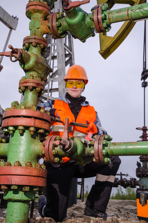 wellhead: Woman engineer in the oil field repairing wellhead with the wrench wearing orange helmet and work clothes. Pump jack background. Oil and gas concept. Stock Photo