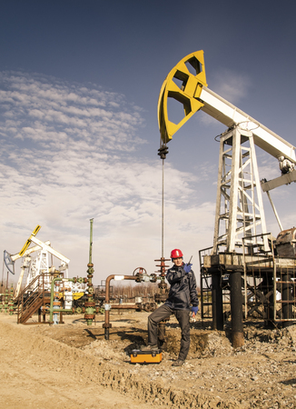 pump jack: Man engineer in the oil field wearing red helmet and work clothes talking on the radio. Pump jack and wellhead background. Oil and gas concept. Toned. Stock Photo