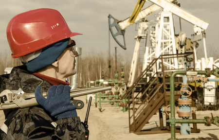 wellhead: Portrait of man engineer in the oil field wearing red helmet and work clothes holding wrenches in his hand and radio in jacket pocket. Blurry pump jack and wellhead background. Oil and gas concept. Toned.
