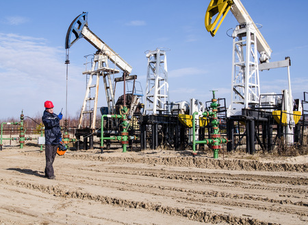 Man engineer in the oil field wearing red helmet and work clothes talking on the radio. Pump jack and wellhead background. Oil and gas concept. Stock Photo