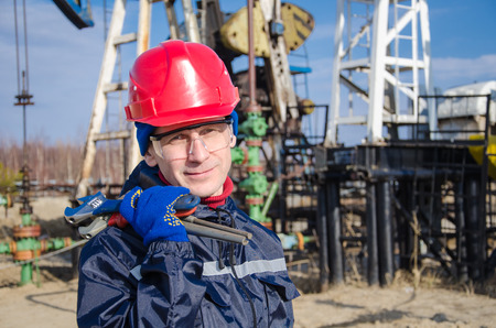 wellhead: Portrait of man engineer in the oil field wearing red helmet and work clothes holding wrenches in his hand. Blurry pump jack and wellhead background. Oil and gas concept.