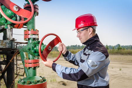 well head: Worker repairing well head valve wearing red helmet and work clothes in the oilfield. Oil and gas concept. Stock Photo