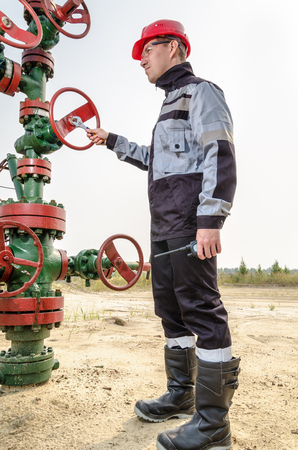 Oilfield worker repairing wellhead valve with the wrench, wearing red helmet and work clothes. Oil and gas concept.