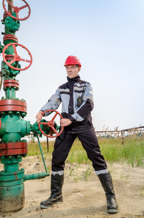 Oilfield worker repairing wellhead valve, wearing red helmet and work clothes with the radio in his pocket. Oil and gas concept.