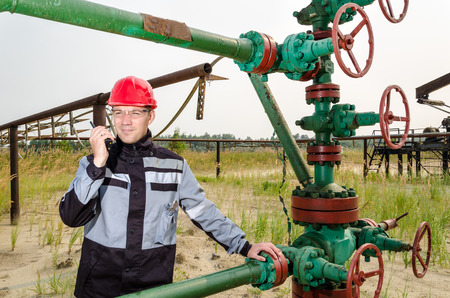 casco rojo: Oilfield worker near wellhead valve, wearing red helmet and work clothes talking on the radio. Oil and gas concept. Foto de archivo