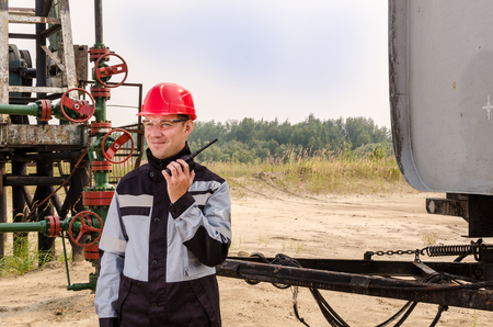 wellhead: Worker talking on the radio near pump jack, wellhead and tank trailer in the oilfield. Oil and gas concept.