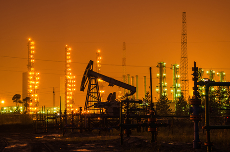 wellhead: Group of oil rigs and wellhead at the background of refinery by night. Oil and gas industry. Stock Photo