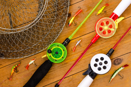 Fishing accessories for winter. Tackles, bait, lure, jig, hook, net. Wooden background. Outdoor activity and leisure concept.