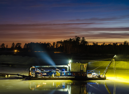 mining ships: Dredger boat working in the lake during sunset. Stock Photo