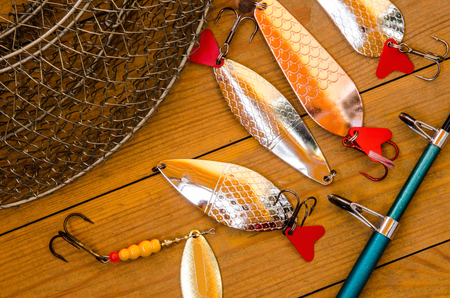 Fishing accessories for summer. Tackle, bait, lure, jig, hook, net. Wooden background. Outdoor activity and leisure concept. Stock Photo