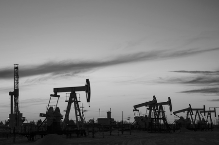 jacks: Pump jacks and derrick silhouette during sunset in the oilfield. Oil and gas concept. Black and white. Stock Photo