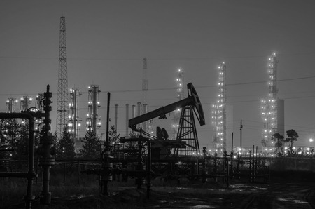 wellhead: Group of oil rigs and wellhead at the background of refinery by night. Oil and gas industry. Black and white.