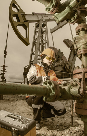 wellhead: Woman engineer in the oilfield repairing wellhead with the wrench and wearing orange helmet and work clothes. Pump jack background. Oil and gas concept.