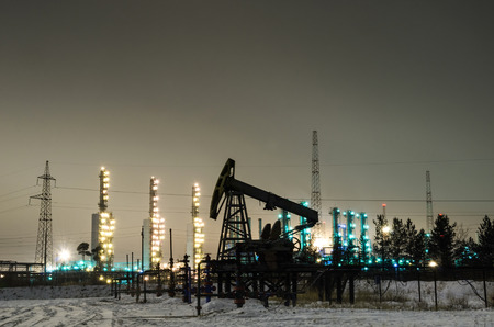 wellhead: Oil pump and wellhead at the background of refinery by night. Oilfield during winter. Oil and gas industry.