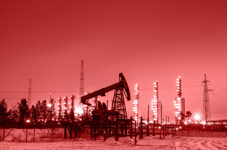 Oil pump and wellhead at the background of refinery by night. Oilfield during winter. Oil and gas industry. Toned. Stock Photo