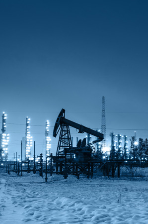 wellhead: Oil pump and wellhead at the background of refinery by night. Oilfield during winter. Oil and gas industry. Toned. Stock Photo