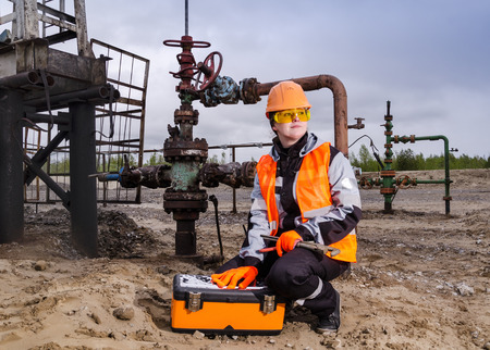 wellhead: Woman engineer in the oilfield repairing wellhead with the wrench wearing orange helmet and work clothes. Oil and gas concept. Stock Photo