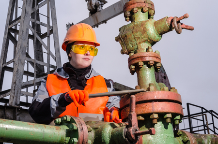 Woman engineer in the oilfield repairing wellhead with the wrench wearing orange helmet and work clothes. Oil and gas concept. Stock Photo