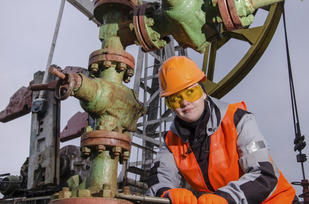wellhead: Woman engineer in the oilfield repairing wellhead with the wrench wearing orange helmet and work clothes. Oil rig background. Oil and gas concept. Stock Photo